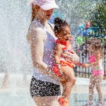 A mother and toddler playing in a spray park.