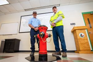 Two men standing behind a red & black fire hydrant