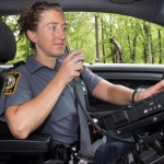 Female officer with laptop computer in vehicle