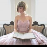 Sarah Walston sits in a pink ball gown with a book on her lap, looking serenely to the left.