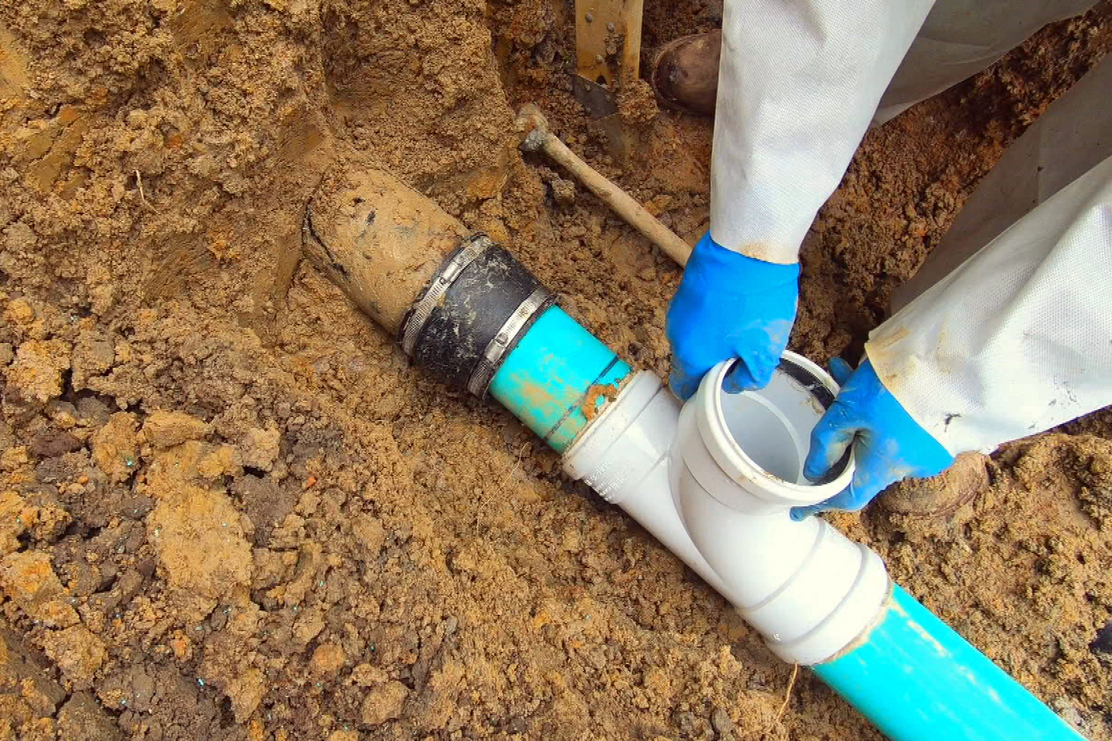 Two gloved hands holding a sewer pipe in the dirt